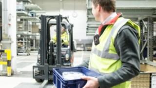 Pessoa equipada com uma unidade móvel do sistema Linde Safety Guard, no recinto da empresa.