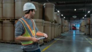 Um colaborador de armazém usa o colete de segurança interativo da Linde Material Handling no armazém escuro
