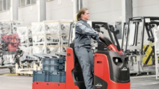 Colaboradora da Linde com trator de reboque no recinto da fábrica