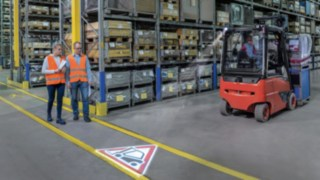 Two people walk in the warehouse and cross with a forklift truck